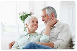 Fotografía de una pareja de ancianos sentados uno junto al otro y tocando la mujer la cara del hombre. La imagen hace referencia al la renta vitalicia