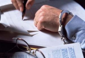 Fotografía de las manos de un hombre de negocios espeposadas por delito mientras firma unos documentos
