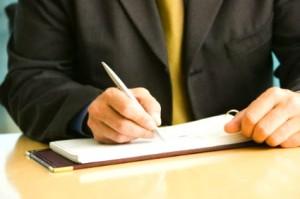 Fotografía de un hombre firmando un pagaré