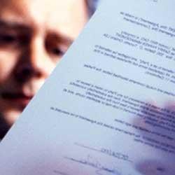 Fotografía de un hombre leyendo un contrato de seguro en referencia a la protección de datos en la Ley de Contrato de Seguro