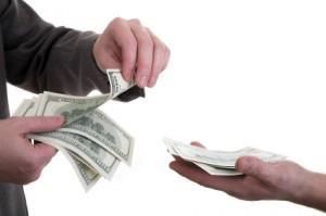 La imagen muestra las manos de dos hombres intercambiandose dinero reflejando un socio que presta dinero a su empresa