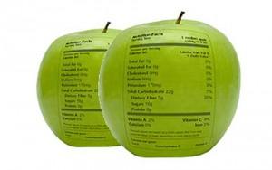 Fotografía de dos manzanas que tienen impresas en su piel dos etiquetas conforme a la ley de etiquetado de productos comerciales