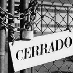 """Fotografía en blanco y negro de una verja cerrada con una cadena y un candado, junto a esto un cartel que pone """"cerrado"""", en referencia a la acción de reclamar pérdidas en la empresa cuando o hay actividad"""