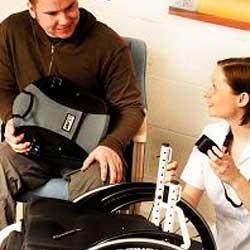 Fotografía de un hombre en sila de ruedas siendo asistido por una enfermera en referencia a la valoración de riesgo