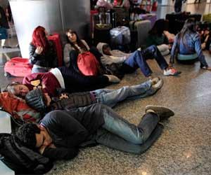 Fotografía de varios viejeros durmiendo en un aeropuerto debido a la cancelación de vuelos