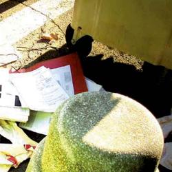 Fotografía en los que aparecen unos documentos junto a un contenedor de basura en referencia a la obtención ilícita de documentos sobre la empresa
