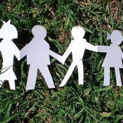 Fotografía de la sirueta de una familia representada en papel sobre un cesped de hierva. La imagen está relacionada con el libro de familia