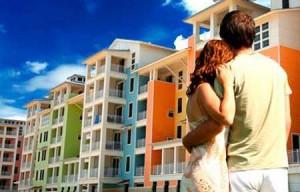 Fotografía de una pareja abrazada mientras miran un bloque de pisos. Esta imagen está relacionada con la reducción del IVA  en la compra de vivienda nueva