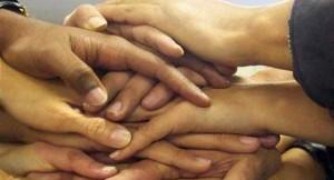 Fotografía de varia manos superpuestas unas sobre las otras en relación a la unión de varios socios minoritarios unidos para el reparto de beneficios de una empresa