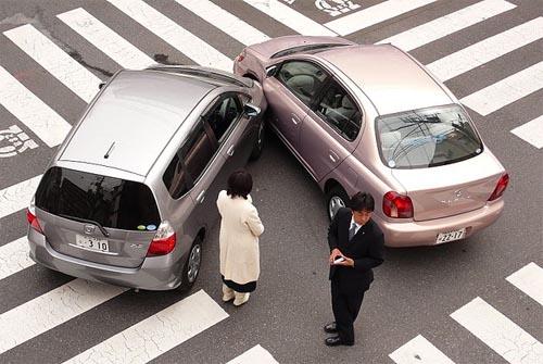 Fotografía de dos coches que han tenido un accidente de tráfico con un choque en su parte frontal y los conductores se encuentran fuera de los vehículos para realizar los trámites