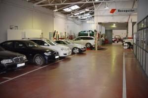 Fotografía de una serie de coches aparcados en un taller. La imagen tiene relación con el avandono de coches en los talleres