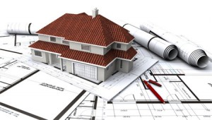 La imagen muestra la maqueta de una casa con unos planos bajo ella en relación con el IVA en la rehabilitación de vivienda