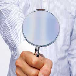 La imagen muestra un hombre vestido de camisa con una lupa en su mano derecha. La imagen está relacionada con la inspección de trabajo para fomentar la contratación