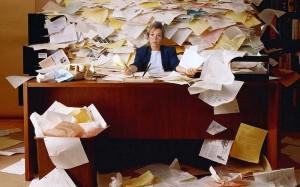 Fotografía de una mujer con el despacho lleno de documentos. Esta imagen hace referencia a la falsedad en documentos mercantiles por particulares