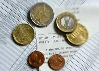 Fotografía de papeles de la Agencia Tributaria y sobre ellos unas monedas de euro y céntimos de euro haciendo referencia a las nuevas retenciones tributarias