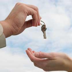 La imagen muestra una fotografía de dos manos en la que una le da unas llaves a la otra, de fondo un cielo azul. Esta imagen hace referencia al derecho de subrogación de las aseguradoras