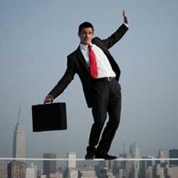 Fotografía de un empresario haciendo equilibrio sobre una cuerda a gran altura. La imagen guarda relación con el riesgo que supone contratar un seguro