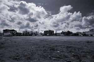 Fotografía en blanco y negro de un descampado donde al fondo se visualizan unos edificios. El descampado es un suelo no urbanizable