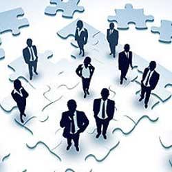 Imagen de un grupo de empresario sobre un puzzle en referencia a las reestructuraciones empresariales