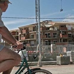 Fotografía de un hombre mayor montando en bicicleta frente a las obras de un edificio en referencia al suelo no urbanizable