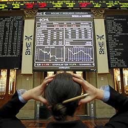 Fotografía de una mujer con las manos en la cabeza por actuar como inversor en bolsa. Frente a ella las gráficas de la bolsa
