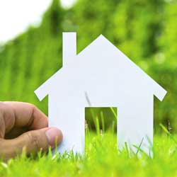 Fotografía de una mano que sujeta una casa de carton en miniatura en un terreno no urbanizado en relación con la futura reforma de Ley de Arrendamientos Urbanos