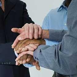 Fotografía de tres personas estrechándose la mano conjuntamente en referencia a la póliza de fianza general