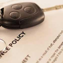 Fotografía de una póliza de seguro y sobre ella las llaves de un coche