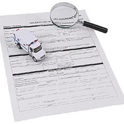 Fotografía de un documento de un seguro y sobre él una lupa y un vehículo en miniatura en relación con el artículo 43 de la LCS