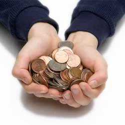 Fotografía de dos manos que contienen un puñado de monedas en relación con la demora en pagos de salarios no da lugar a la resolución del contrato