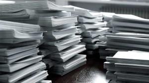 Fotografía de varios montones de papeles acumulados unos sobre otros en referencia al depósito de las cuentas anuales en el Registro Mercantil
