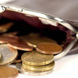 Fotografía de un monedero del que salen monedas en referencia a la reforma en los delitos en hacienda pública y seguridad social
