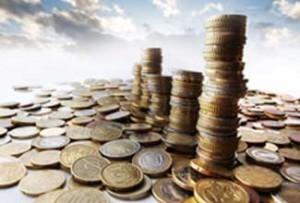 Fotografía de un suelo formado por monedas euros y céntimos de euros y sobre él varias torres fomadas también por monedas haciendo referencia al impuesto sobre sociedades