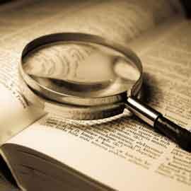 Fotografía de un libro abierto con una lupa sobre él en referencia al contrato de seguro en el transporte terrestre
