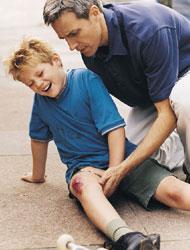 Fotografía de un niño que se ha caido en la calle y se ha dañado la rodilla derecha mientras su padre le asiste. La fotografía guarda relación con la indemnización de un ayuntamiento a un menor accidentado en la calle