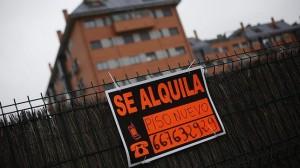 """Fotografía de un cartel de """"Se alquila"""" y al fondo se vé un edificio. La imagen está relacionada con la nueva ley de alquileres creada para fomentar los alquileres en España"""