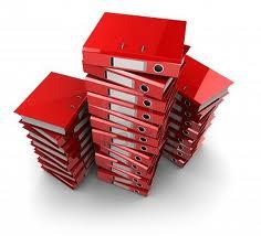 Fotografía de varios archivadores rojos colocados unos encima de los otros en referencia a la liquidacion de gananciales