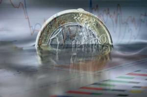 Fotografía de un euro sumergido en unas gráficas que hacen referencia a las nuevas medidas fiscales de 2013