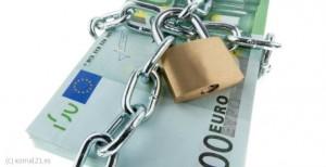 Fotografía de unos billetes de cien euros en efectivo rodeados por una cadena y un candado