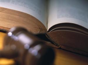 Fotografía de un libro jurídico junto a el mazo de un juéz en referencia a los juicios de lo contencioso administrativo