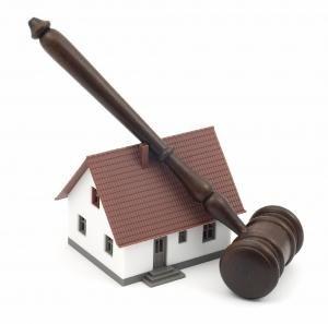 Imagen de una casa en miniatura con el mazo de un juez sobre ella en relación con la nulidad de la normativa española de desahucio