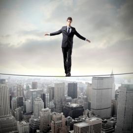 Fotografía de un hombre de chaqueta y corbata haciendo equilibrio en una cuerda sobre una ciudad de rascacielos. La imagen trata de reflejar el siniestro en seguro de responsabilidad civil profesional
