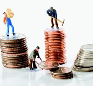 Fotografía de unas figuras de obreros en miniatura que trabajan moviendo monedas de céntimo de euro en referencia a la retribución a la carta