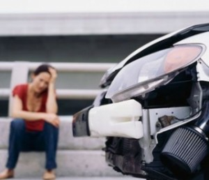 Fotografía de la parte frontal de un coche accidentado y de fondo la conductora del siniestro