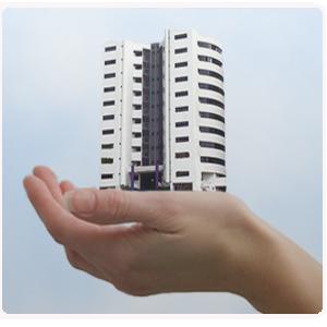 Fotografía de una mano sujetando un edificio aludiendo a la cláusula delimitadora en el seguro de comunidades