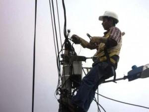 Un empleado electrico reparando los cables de la luz en relación con el seguro de Industria y la indemnización por daños en la energía eléctrica