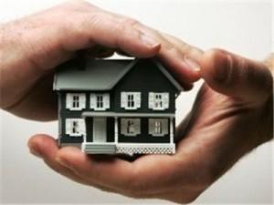 Fotografía de una casa en miniatura envuelta en dos manos en referencia al artículo de la Ley de Contrato de Seguro