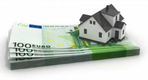 Imagen de una casa en miniatura sobre un puñado de billetes de cien euros. Esta imagen está relacionada con la nulidad de la cláusula de suelo en la hipoteca