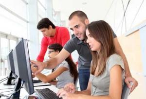 Fotografía de un empleado de una empresa mostrando a otra empleada como realizar el trabajo en el ordenador. La imagen tiene relación con el contrato de formación