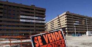 """Fotografía de un cartel de """"Se vende"""" y de fondo varios edificios con viviendas vacías"""